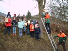 gemeinsam mit den Schülern der Schule Leutenberg bringen die Mitarbeiter der Naturparkverwaltung Nistkästen für Vögel an Bäumen an Beate Graumann